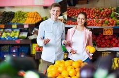 Donkerbruine meisje en het glimlachen vriend het kopen citrusvruchten Royalty-vrije Stock Afbeeldingen