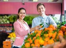 Donkerbruine meisje en het glimlachen vriend het kopen citrusvruchten Stock Foto