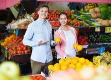 Donkerbruine meisje en het glimlachen vriend het kopen citrusvruchten Stock Afbeelding