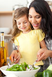 Donkerbruine moeder die haar dochter helpt salade voorbereiden Stock Afbeeldingen