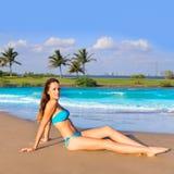 Donkerbruine toeristenzitting in strandzand gelukkig looien Stock Afbeelding