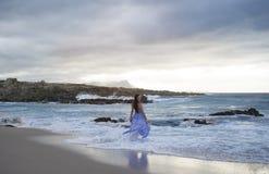Donkerbruine vrouw in blauwe status in oceaan Royalty-vrije Stock Foto's