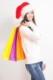 Donkerbruine vrouw in de holding van de santahoed het winkelen zakken Stock Afbeeldingen