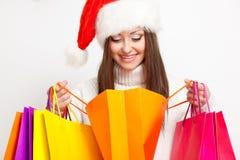 Donkerbruine vrouw in de holding van de santahoed het winkelen zakken Stock Foto's