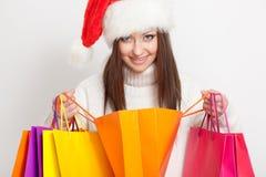 Donkerbruine vrouw in de holding van de santahoed het winkelen zakken Royalty-vrije Stock Foto
