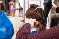Donkerbruine Vrouw die Bruin Haar Droog in Salon hebben stock foto