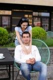 Donkerbruine vrouw die echtgenootzitting als voorzitter buiten koesteren bij straatkoffie Stock Afbeeldingen
