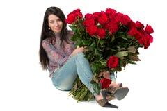 Donkerbruine vrouw die een groot boeket van rode rozen houden stock fotografie