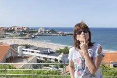 Donkerbruine vrouw die een kus voor een zeebedding, strand in Ca werpen stock afbeelding