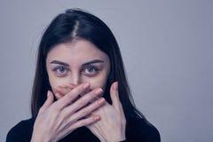 Donkerbruine vrouw die gezicht behandelen die haar gebruiken beide handen Royalty-vrije Stock Afbeeldingen