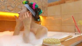 Donkerbruine vrouw die gezichtsmasker in schuimend bad gebruiken Schoonheidsbehandelingen thuis 4K video stock videobeelden