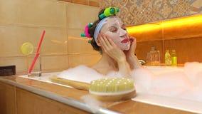 Donkerbruine vrouw die gezichtsmasker in schuimend bad toepast Schoonheidsbehandelingen thuis 4k schot stock video