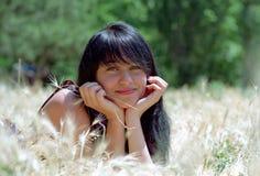 Donkerbruine vrouw die in gras ligt stock foto's