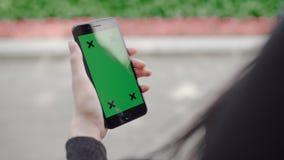 Donkerbruine vrouw die mobiele telefoon met de groene sleutel van de het schermchroma met behulp van stock footage