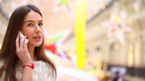 Donkerbruine vrouw die op celtelefoon spreken stock footage