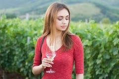 Donkerbruine vrouw die pret in de wijngaarden hebben stock afbeelding