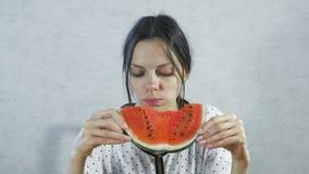 Donkerbruine vrouw die sappige watermeloen op witte achtergrond eten stock videobeelden