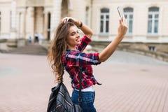 Donkerbruine vrouw die selfie met mobiele telefoon nemen die langs de straat met rugzak lopen Royalty-vrije Stock Foto