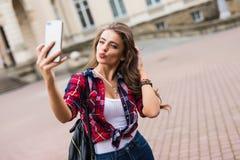 Donkerbruine vrouw die selfie met mobiele telefoon nemen die langs de straat met rugzak lopen Royalty-vrije Stock Foto's