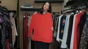 Donkerbruine vrouw die sweater kiezen van rek met hangers binnen ruimte stock videobeelden