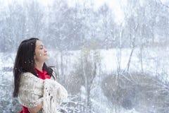 Donkerbruine vrouw die van de sneeuwval genieten royalty-vrije stock afbeeldingen