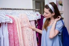 Donkerbruine vrouw die voor kleren winkelen stock foto's