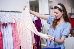 Donkerbruine vrouw die voor kleren winkelen stock afbeelding
