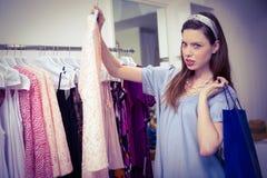 Donkerbruine vrouw die voor kleren winkelen stock fotografie
