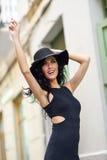 Donkerbruine vrouw die zwarte verleidelijke kleding in de straat dragen Stock Afbeeldingen
