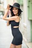 Donkerbruine vrouw die zwarte verleidelijke kleding in de straat dragen Stock Fotografie