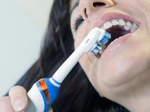 Donkerbruine vrouw het borstelen tanden met elektrische tand Stock Foto's