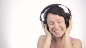 Donkerbruine vrouw het luisteren muziek met grote hoofdtelefoons en het dansen op een lichte achtergrond stock videobeelden