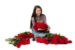 Donkerbruine vrouw met een groot boeket van rode rozen royalty-vrije stock afbeelding