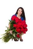 Donkerbruine vrouw met een groot boeket van rode rozen stock foto's