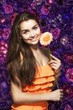 Donkerbruine vrouw met een zachte samenstelling die de camera terwijl het houden van bloem dichtbij het gezicht op een bloemenach Stock Foto's
