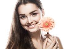 Donkerbruine vrouw met een zachte samenstelling die de camera terwijl het houden van bloem dichtbij het gezicht op geïsoleerd bek Stock Afbeeldingen