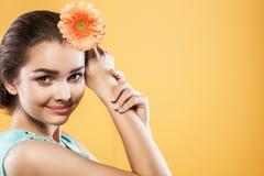 Donkerbruine vrouw met een zachte samenstelling die de camera terwijl het houden van bloem dichtbij het hoofd op gele achtergrond Stock Afbeeldingen