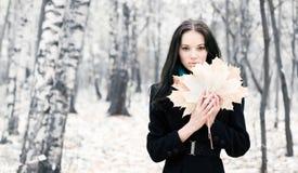 Donkerbruine vrouw met esdoornbladeren Royalty-vrije Stock Afbeelding