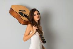 Donkerbruine vrouw met gitaar in handen Stock Foto