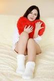 Donkerbruine vrouw met harthoofdkussen Stock Foto