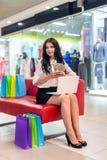 Donkerbruine vrouw met laptop, het winkelen zakken en dollars royalty-vrije stock afbeelding