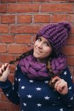Donkerbruine vrouw in purpere gebreide hoed en sjaal Stock Afbeelding