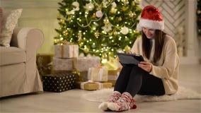 Donkerbruine Vrouw in Santa Hat Using Tablet, die op het Tapijt op de Vloer naast Kerstboom zitten Glimlachend meisje met stock video
