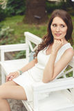 Donkerbruine vrouw in witte kledingszitting op bank in park Royalty-vrije Stock Afbeeldingen