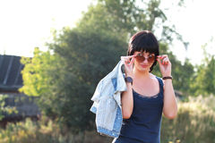 Donkerbruine vrouw in zonnebril met denimjasje Royalty-vrije Stock Fotografie
