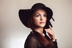 Donkerbruine vrouw in zwarte kleding en hoed Stock Fotografie