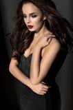 Donkerbruine vrouw in zwarte kleren stock fotografie
