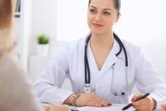 Donkerbruine vrouwelijke arts die aan patiënt in het het ziekenhuisbureau spreken De arts zegt over medische examens resultaten v Stock Fotografie