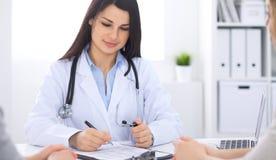 Donkerbruine vrouwelijke arts die aan patiënt in het het ziekenhuisbureau spreken De arts zegt over medische examens resultaten v Stock Afbeelding