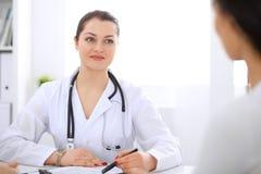 Donkerbruine vrouwelijke arts die aan patiënt op het ziekenhuiskantoor spreken De arts zegt over medische examens resultaten voor Royalty-vrije Stock Fotografie